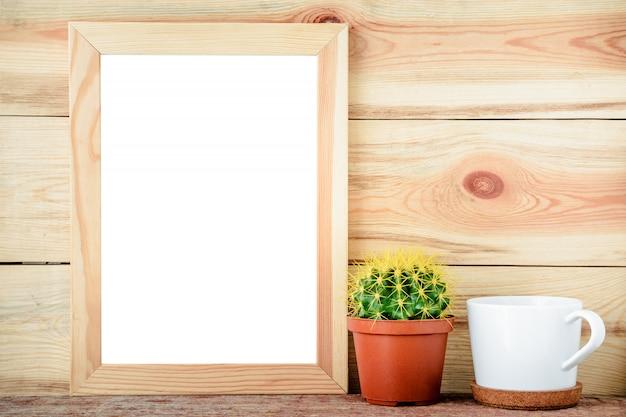 Svuoti la struttura di legno con il cactus e la tazza bianca su fondo di legno Foto Premium