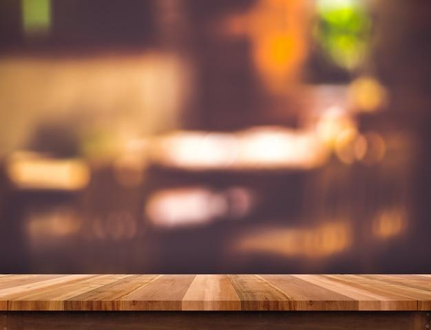 Svuoti la tavola di legno marrone e il fondo vago della luce del bokeh del ristorante Foto Premium