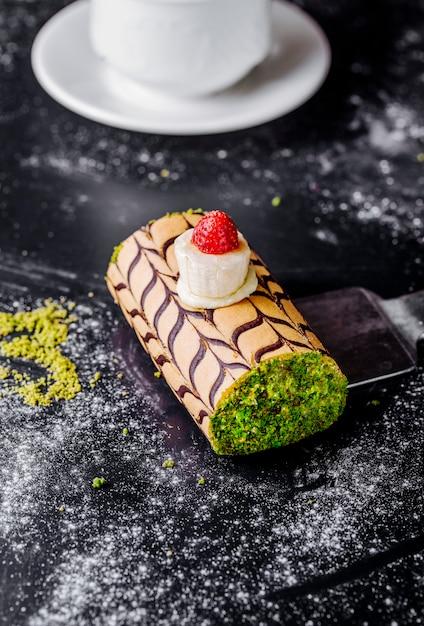 Swiss roll cake con pistacchio tritato e crema alla vaniglia con ciliegia. Foto Gratuite