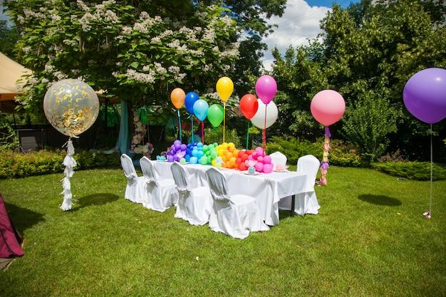 Tabella di compleanno con palloncini arcobaleno. vacanze estive nel parco. Foto Premium