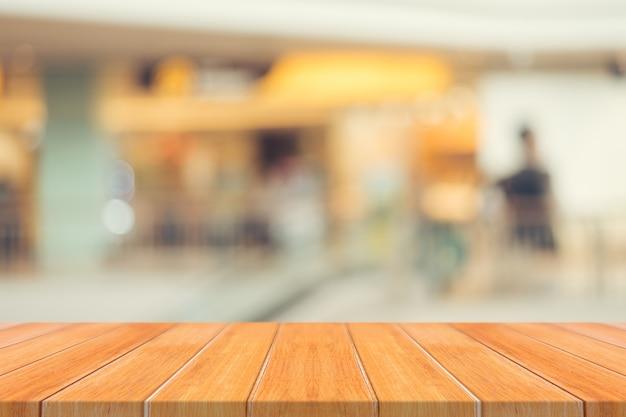 Tabella di legno tabella vuota offuscata priorità bassa. prospettiva legno marrone sopra sfocatura nel grande magazzino - può essere utilizzato per la visualizzazione o il montaggio dei vostri prodotti.cassa per la visualizzazione del prodotto. Foto Gratuite
