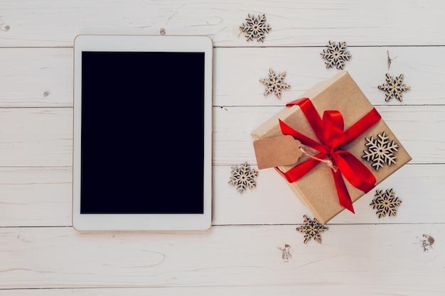 Tabella di vista superiore, e confezione regalo con fiocchi di neve su sfondo bianco di legno per natale e nuovo anno. natale e capodanno concetto. Foto Premium
