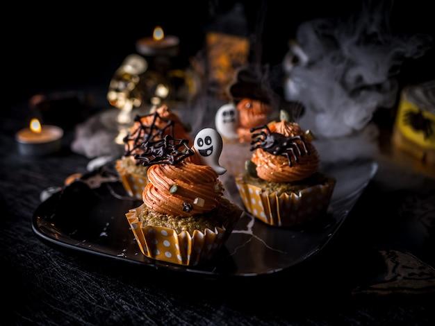 Tabella operata del partito dell'alimento di halloween con il muffin e i biscotti del bigné della zucca. Foto Premium