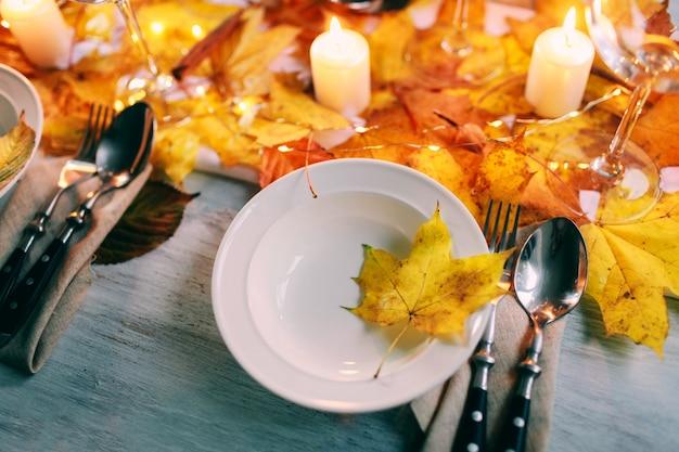 Tabella servita con decorazioni, candele e foglie d'autunno Foto Premium