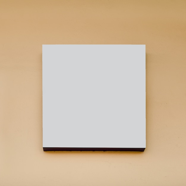 Tabellone per le affissioni di forma quadrata bianca su fondo beige Foto Gratuite