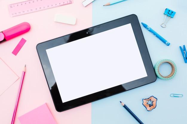 Tablet con elementi decorativi intorno su sfondo colorato Foto Gratuite