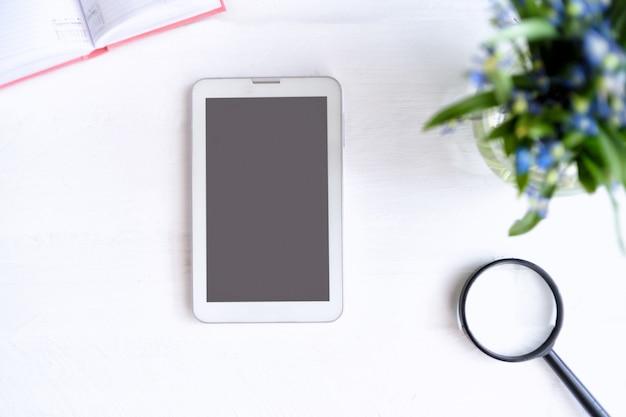Tablet con schermo nero vuoto. taccuino, lente d'ingrandimento e fiori sul tavolo Foto Premium