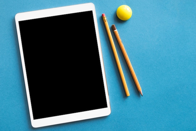 Tablet e matite sulla superficie blu Foto Gratuite
