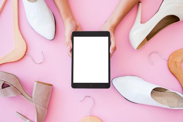 Tablet vista dall'alto circondato da scarpe Foto Gratuite