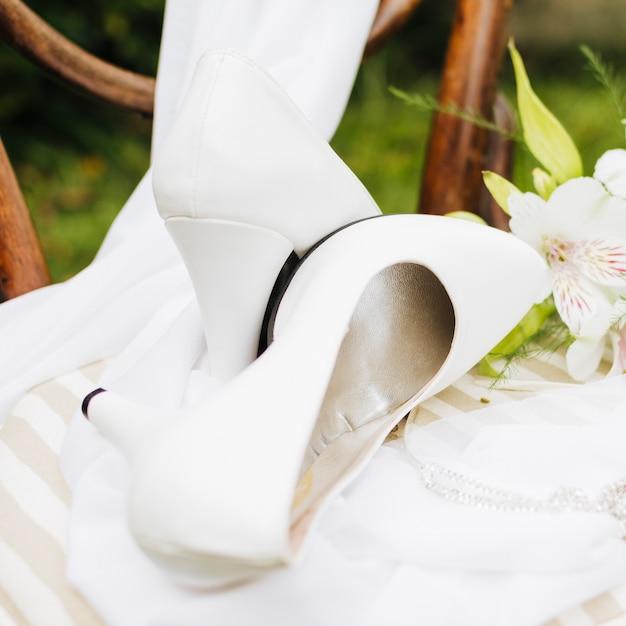 Tacchi alti bianchi sopra la sciarpa sul tavolo bianco Foto Gratuite