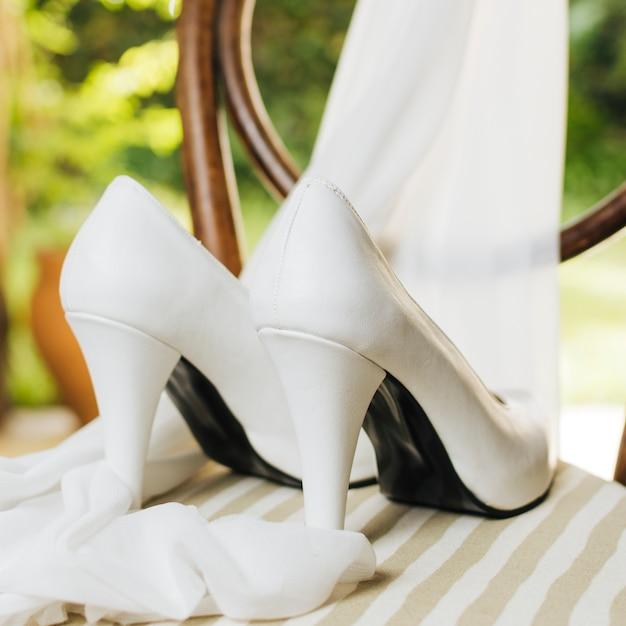 Tacchi alti da sposa con sciarpa sul tavolo Foto Gratuite