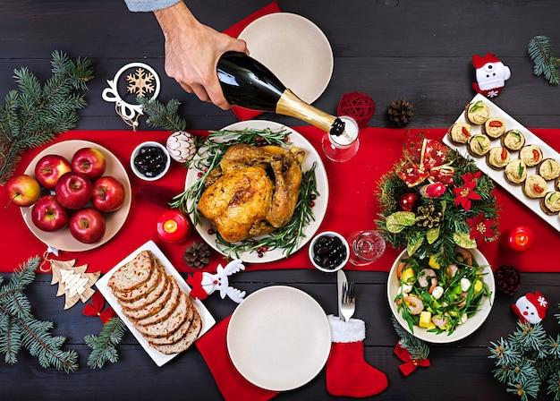 Tacchino al forno. cena di natale. la tavola di natale è servita con un tacchino, decorato con orpelli luminosi e candele. pollo fritto, tavolo. cena di famiglia. vista dall'alto Foto Gratuite