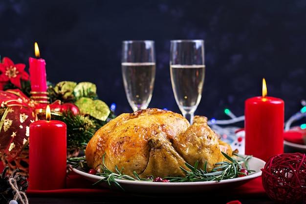 Tacchino al forno il tavolo di natale è servito con un tacchino, decorato con tinsel luminoso Foto Premium