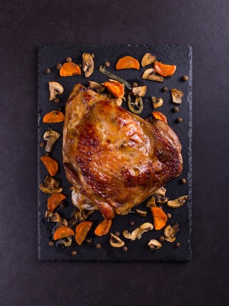 Tacchino coscia al forno con spezie su pietra nera sullo sfondo Foto Premium