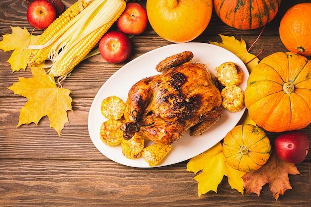 Tacchino festivo o pollo al forno del ringraziamento sul piatto bianco e un raccolto di verdure di stagione: mele mais zucca Foto Premium