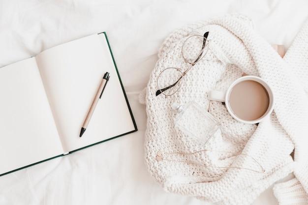 Taccuino aperto con la penna vicino al maglione con le cose sul lenzuolo Foto Gratuite