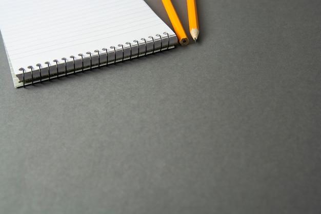 Taccuino con la matita su sfondo grigio. istruzione, affari con lo spazio della copia. modello. Foto Premium