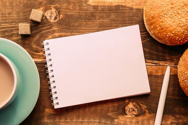 Taccuino con una penna sul tavolo accanto al cacao Foto Premium