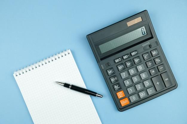 Taccuino controllato con libro bianco e penna, grande calcolatore nero su fondo blu. Foto Premium