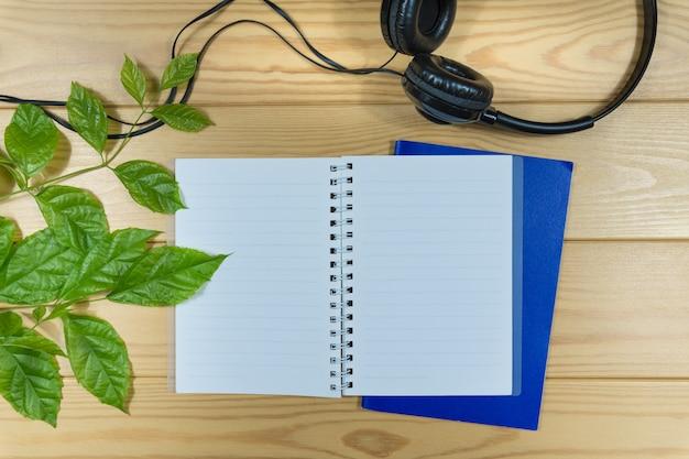 Taccuino, cuffia e ramo di foglie verdi sul tavolo di legno. Foto Premium