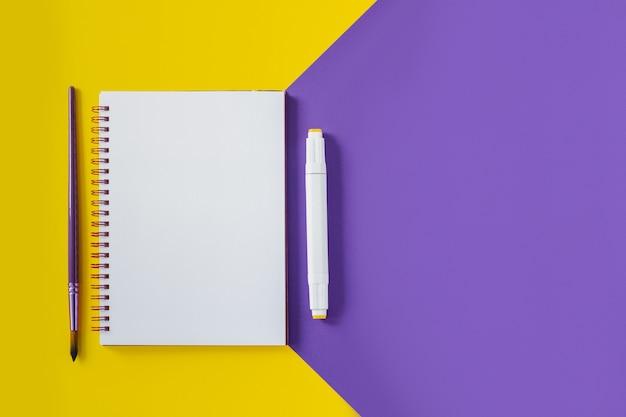 Taccuino della scuola sul blocco note a spirale giallo e porpora, su una tavola. sfondo vista dall'alto con copyspace. blocco note per ufficio disteso. Foto Premium