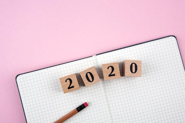 Taccuino di nuovo anno 2020 su sfondo rosa Foto Premium
