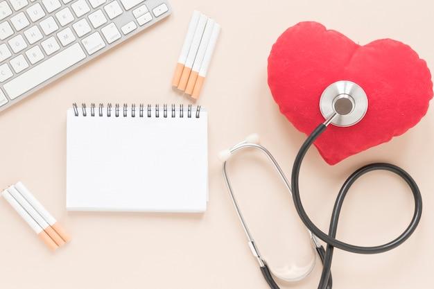 Taccuino di vista superiore con cuore e stetoscopio Foto Gratuite