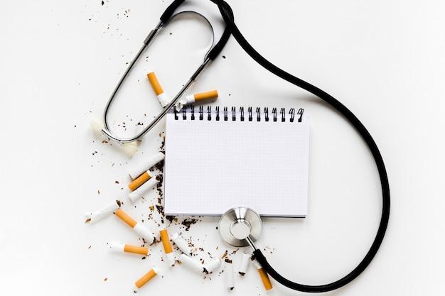 Taccuino di vista superiore con le sigarette e lo stetoscopio Foto Gratuite