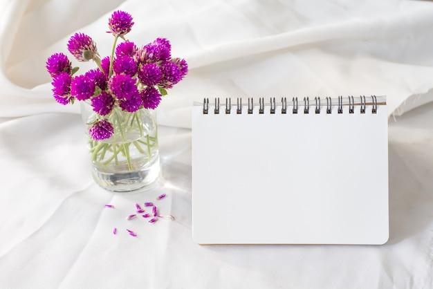 Taccuino e fiore viola sul tavolo Foto Premium