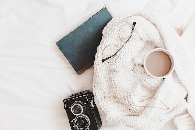Taccuino e macchina fotografica vicino al maglione con le cose sul lenzuolo Foto Gratuite