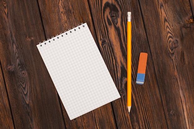 Taccuino e matita in bianco su una superficie di legno Foto Premium