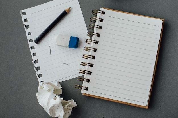 Taccuino e matita su sfondo grigio Foto Premium