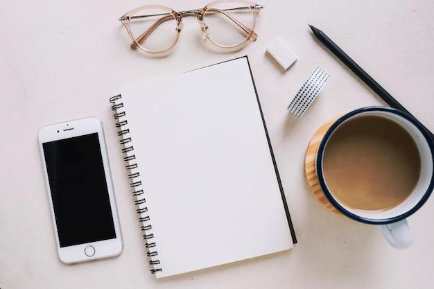 Taccuino e occhiali vicino a smartphone e caffè Foto Gratuite