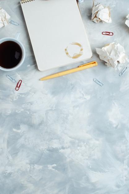 Taccuino e tazza di caffè sopra priorità bassa concreta Foto Premium