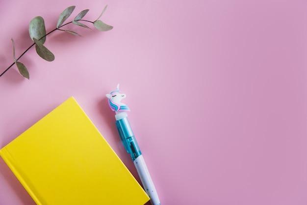 Taccuino giallo per note, penna unicorno divertente e foglie di eucalipto verde su sfondo rosa pastello. disteso. vista dall'alto. copia spazio Foto Premium