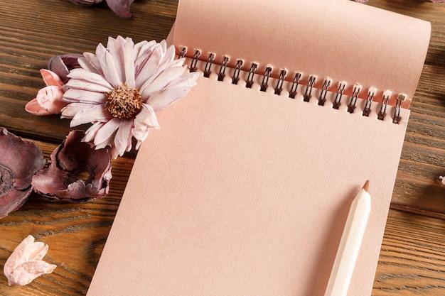 Taccuino in bianco con il fiore sulla tavola di legno d'annata Foto Premium