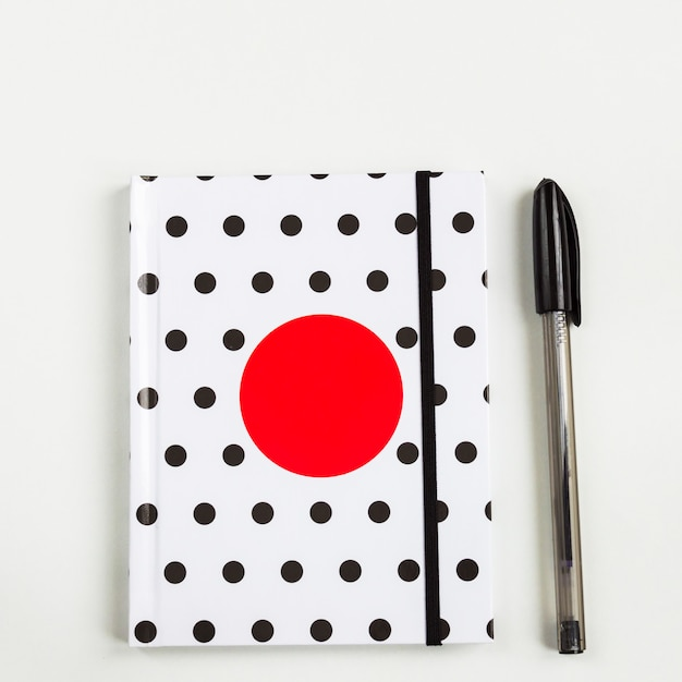 Taccuino in bianco e nero a pois con il cerchio rosso sulla copertina e penna nera sulla tavola bianca. vista dall'alto, minima planarità Foto Premium