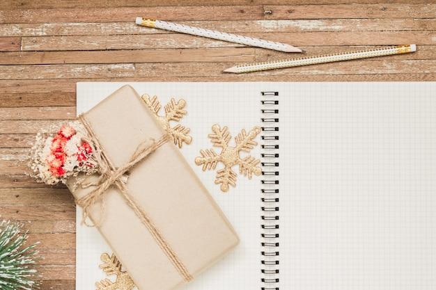 Taccuino in bianco su legno con gli ornamenti di natale e il contenitore di regalo Foto Premium
