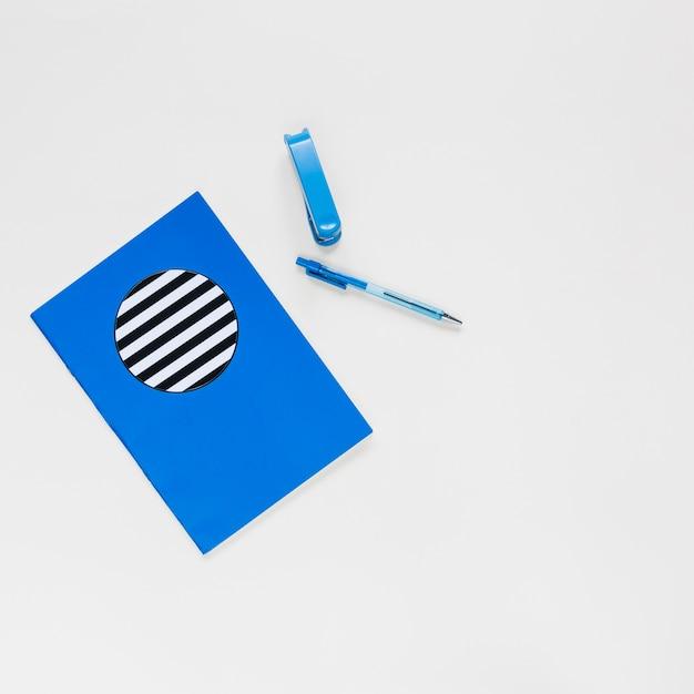Taccuino; penna e spillatrice su sfondo bianco Foto Gratuite