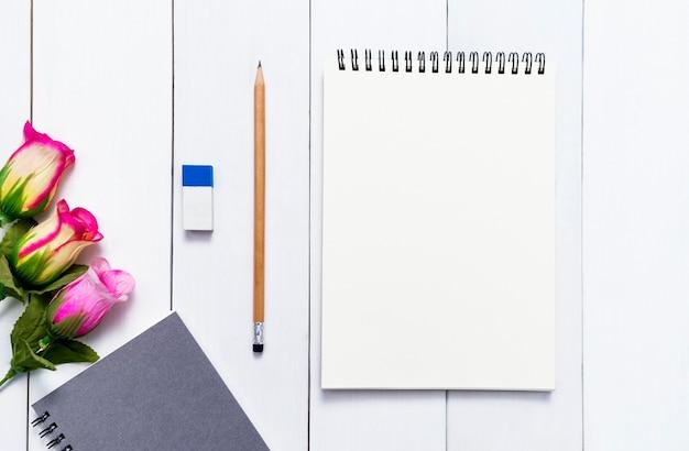 Taccuino per derisione con sullo sfondo di tavolo in legno bianco Foto Premium