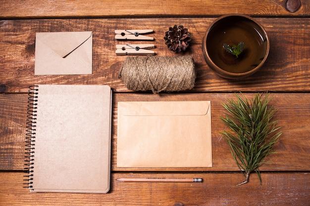 Taccuino per ricette, busta di carta, corda e mollette sul tavolo di legno. Foto Gratuite