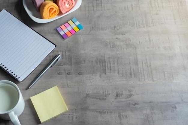 Taccuino, smartphone, rotolo di marmellata, tazza di latte, penna su legno, nota di carta affare, concetto di istruzione e progettazione Foto Premium