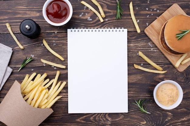 Taccuino sul tavolo con hamburger e patatine fritte Foto Gratuite