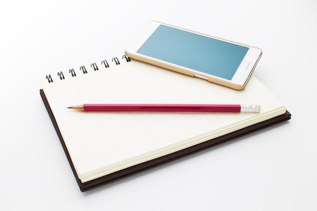 Taccuino, telefono e matita isolati su fondo bianco. Foto Premium