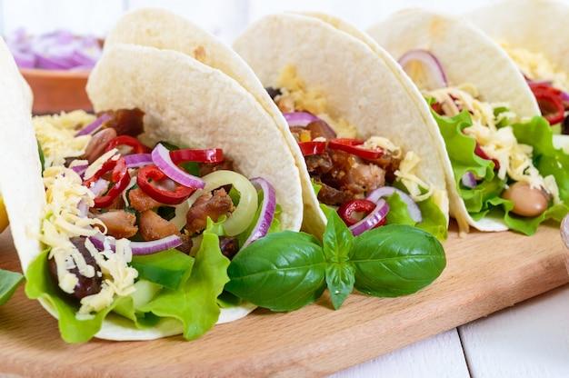 Tacos è un piatto messicano tradizionale. tortilla ripiena di pollo, campana e peperoncino, fagioli, lattuga, formaggio, cipolla blu con salsa di salsa su fondo di legno bianco. Foto Premium