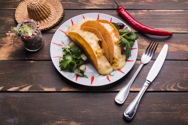 Tacos fra le verdure sul piatto vicino al peperoncino rosso e al sombrero Foto Gratuite