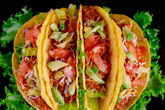 Tacos messicani con carne e verdure sulla banda nera su fondo di legno Foto Premium