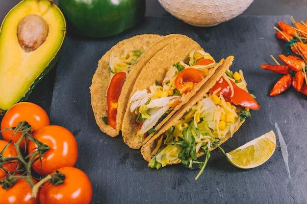 Tacos messicani di manzo con verdure; pomodoro; avocado su ardesia nera Foto Gratuite