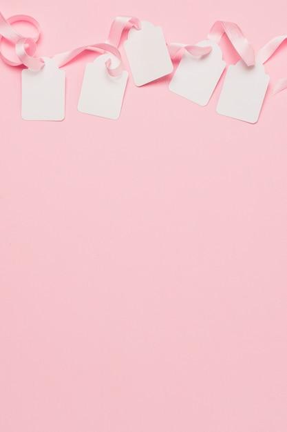 Tag bianco e nastro rosa nella parte superiore dello sfondo con lo spazio per il testo Foto Gratuite