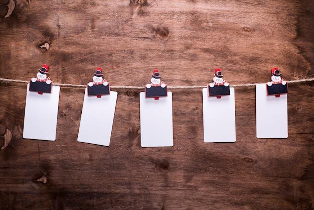 Tag di carta appeso a una corda agganciata su mollette di natale decorativi Foto Premium